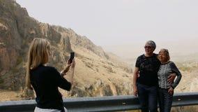 Córka bierze fotografię telefonem komórkowym jej starsi rodzice na urlopowej wycieczce w górach przy drogową przerwą szczęśliwa r zbiory wideo