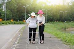 Córka bierze opiece starszego kobiety odprowadzenie na ulicie fotografia stock