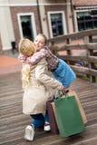 Córka ściska jej matki z torba na zakupy na drewnianym moscie Zdjęcia Stock