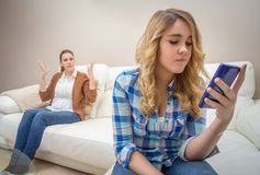 Córka patrzeje telefon i ignoruje jej matki zdjęcia stock