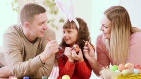 Córka trzyma kurczaka jajko, i ona rodzice dekoruje je i wszystkie spojrzenie przy ojcem zbiory wideo