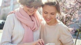 C?rki i matki li?? przez fotografii w smartphone Portret na pogodnej wiosny ulicie dzie? kwiat daje mum syna matkom zdjęcie wideo
