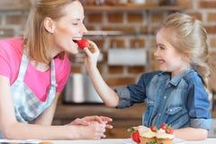 Córki karmienia matka z truskawką od babeczki fotografia royalty free