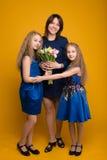 Córki Życzą mamie szczęśliwego wakacyjnego bukiet kwiaty zdjęcia stock
