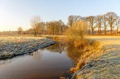 Córrego curvado em uma paisagem invernal cedo na manhã Foto de Stock Royalty Free