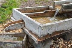 Córrego da água alpina fresca que corre através de chu de madeira feito a mão fotografia de stock