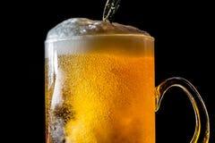 Córrego da cerveja que derrama em um vidro com cerveja e na espuma isolada no fundo preto, textura do close up Imagens de Stock