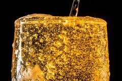 Córrego da cerveja que derrama em um vidro com cerveja e na espuma isolada no fundo preto, textura do close up Fotografia de Stock Royalty Free