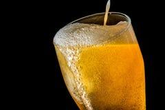 Córrego da cerveja que derrama em um vidro com cerveja e na espuma isolada no fundo preto, textura do close up Foto de Stock