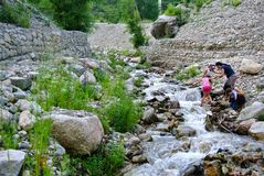 Córrego da montanha e duas mulheres asiáticas com suas crianças na costa rochosa kazakhstan imagem de stock