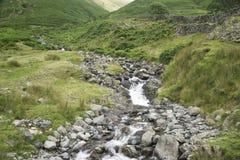 Córrego do enrolamento através dos montes Imagem de Stock