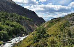 córrego Geleira-alimentado entre montes verdes no Patagonia, o Chile de Torres del Paine imagem de stock