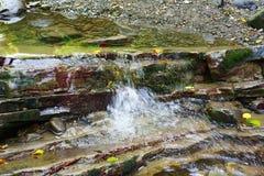 Córrego puro de fluxos da angra da montanha entre as rochas imagens de stock royalty free