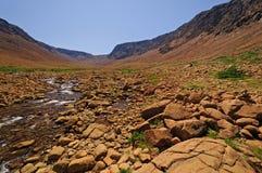 Córrego que corre através de montes áridos Foto de Stock