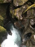 Córrego que emerge das rochas fotografia de stock
