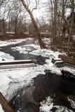 Córrego que passa sobre a represa no inverno Fotos de Stock Royalty Free