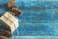 cône de boîte-cadeau et de pin sur le fond des conseils en bois bleus Photo stock