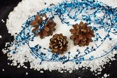 Cône de trois pins sur la neige avec le fil d'étoile bleue Images libres de droits