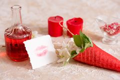 cône rouge de gaufre avec des fleurs, baiser d'amour sur le papier, message et cadeau, vin et des bougies Photographie stock libre de droits