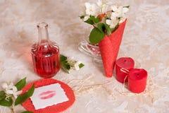 cône rouge de gaufre avec des fleurs, baiser d'amour sur le papier, message et cadeau, vin et des bougies Photos stock
