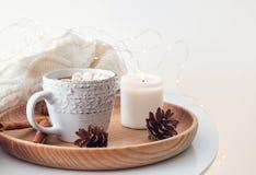 Cônes chauds de cacao, de bougie et de pin sur le plateau en bois Images libres de droits