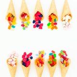 Cônes de gaufre avec la sucrerie lumineuse colorée sur le fond blanc Configuration plate, vue supérieure Photo stock