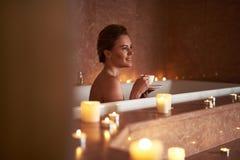 Côté dessus de thé de sourire heureux de boissons de dame dans le bain photographie stock libre de droits