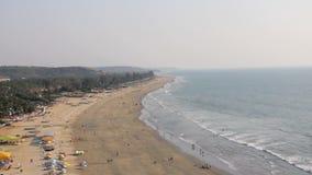 Côte avec des personnes marchant le long d'une plage sablonneuse contre un océan bleu banque de vidéos