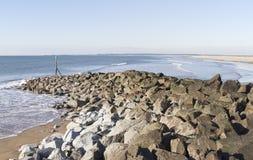 Côte avec le brise-lames de roche au Dinas Dinlle Image libre de droits