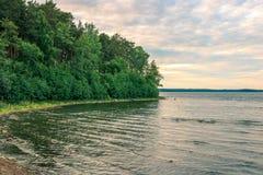 Côte boisée d'un lac tranquille sous un ciel nuageux Oriental - paysage européen image libre de droits