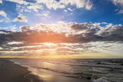 Côte de mer baltique avec les nuages scéniques de cumulus et de stratocumulus sur le ciel au coucher du soleil image stock