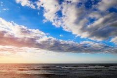 Côte de mer baltique avec les nuages scéniques de cumulus et de stratocumulus sur le ciel au coucher du soleil photos stock