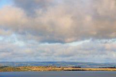 Côte du lac avec des cumulus images stock