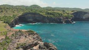 Côte rocheuse à côté de la plage cassée sur l'île de Nusa Penida Vidéo de bourdon Silhouette d'homme se recroquevillant d'affaire banque de vidéos