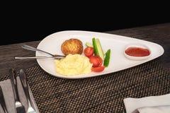 Côtelette avec des pommes de terre gruau et légumes d'un plat blanc Photo stock