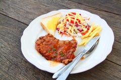 Côtelette de porc avec les frites et la salade photos libres de droits