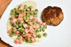 Côtelette et pois faits maison frits avec des carottes dans le sauceon crémeux un plat blanc images libres de droits