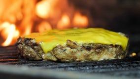 Côtelette grillée avec du fromage, hamburger, côtelette d'hamburger, dans la flamme de fond et la fumée, tir en gros plan banque de vidéos
