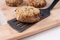 Côtelette panée sur la spatule et deux petits pâtés supplémentaires photo stock