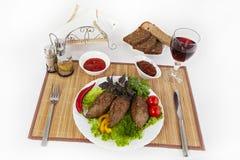 Côtelettes avec des verts, des tomates et des concombres Servez avec du pain noir ou blanc et un verre de vin rouge photo libre de droits