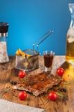 Côtes découvertes de BBQ d'un gril de charbon de bois sur le fond bleu photos libres de droits