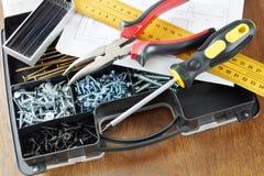 Cążki i śrubokręt kłamają na plastikowym organizatorze z wiele śrubami Fotografia Stock