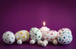 Cętkowani jajka duzi ones i mali ones z zaświecającą świeczką na purpurach Fotografia Royalty Free