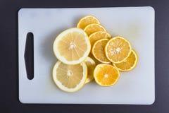 c新鲜的健康桔子样式维生素 切片柠檬和桔子在被削减的委员会 柑橘水果在委员会被切 图库摄影