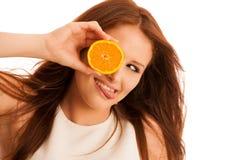 C维生素妇女-女孩用在她的面孔前面的橙色果子 免版税库存照片