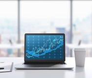 C'è un computer portatile con il grafico dei forex sullo schermo, blocco note e una tazza di caffè sulla tavola Un posto di lavor Fotografia Stock