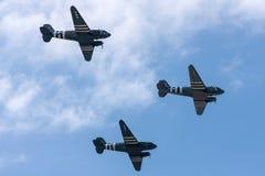C-47 ρεύμα-3 Ντάγκλας εποχής Δεύτερου Παγκόσμιου Πολέμου τρία αεροσκάφη μεταφορών με τα λωρίδες εισβολής μέρας-μ που πετούν στο σ στοκ φωτογραφία με δικαίωμα ελεύθερης χρήσης