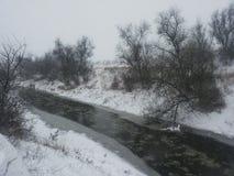 33c 1月横向俄国温度ural冬天 在冬天暴风雪中的一条小河 与一条河的明信片在冬天 低温 冻结河 库存图片