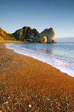 C-00152. Warm light at sunset on the Dorset coast looking East towards Durdle Door with a clear blue sky stock photos