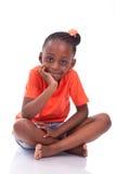 逗人喜爱的矮小的非裔美国人的女孩坐地板-黑c 图库摄影
